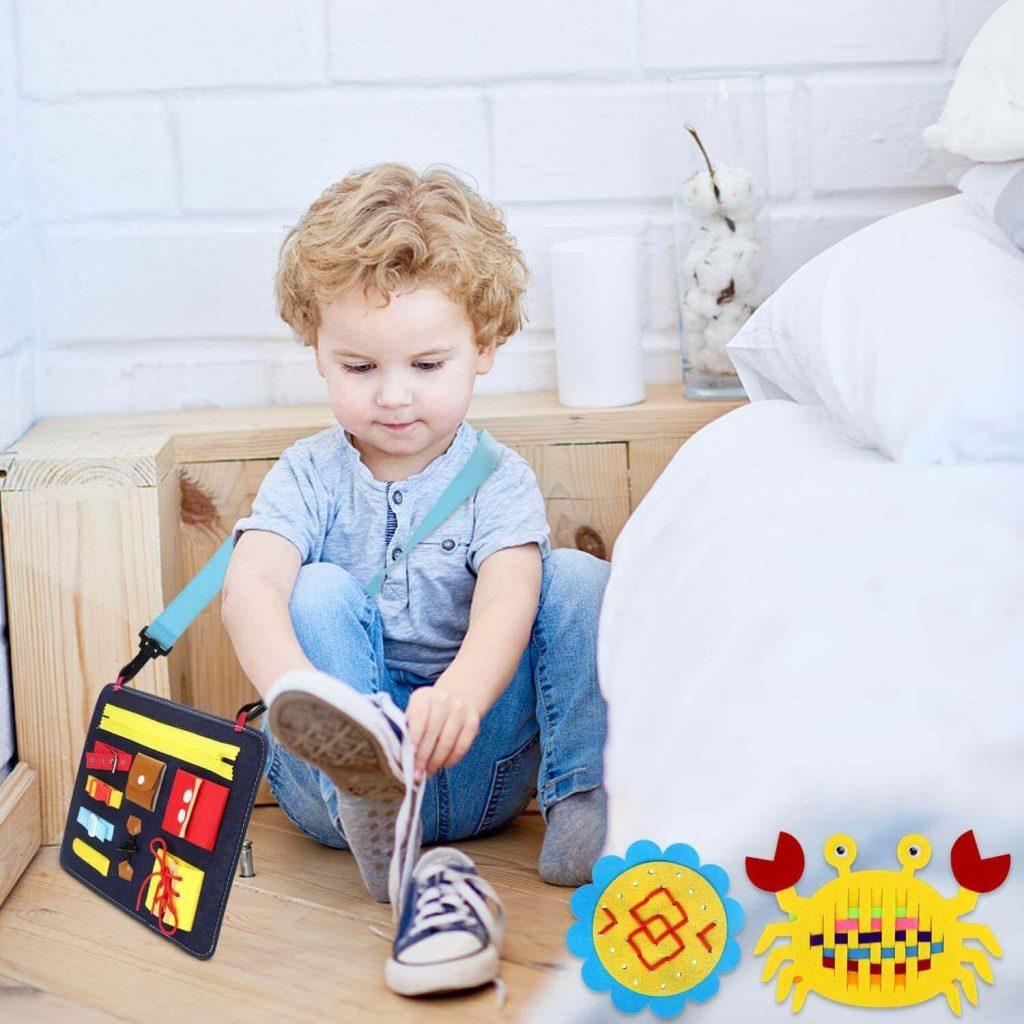 niño jugando con su busy board Montessori