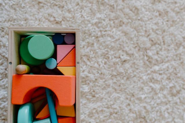 Juguetes y muebles tipo Montessori ordenados en una caja de madera