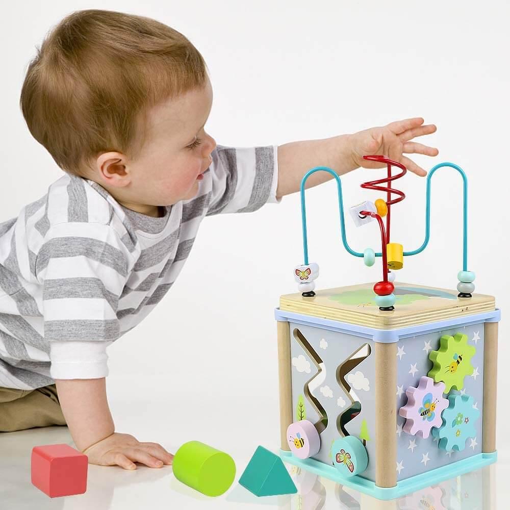 Niño jugando cubo de actividades Montessori