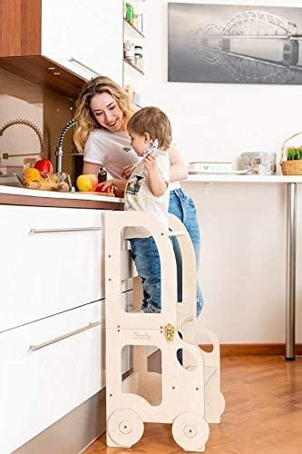 niño en la cocina en su torre de aprendizaje Montessori
