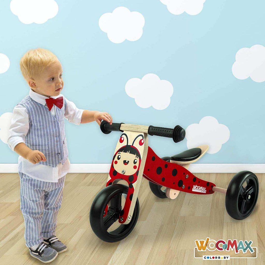 Niño jugando con triciclo de madera
