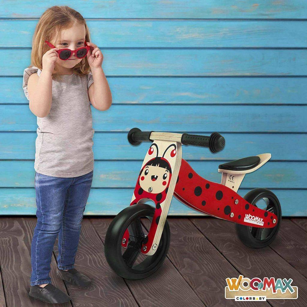 niña mirando su triciclo Montessori